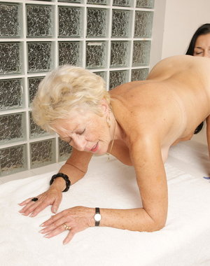 Three old and young lesbians have fun on the massage table