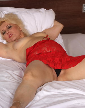 This horny blonde mature minx is getting wet on her bed