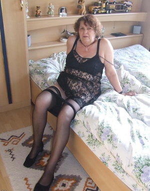 Horny mama playing with a dildo on her bed