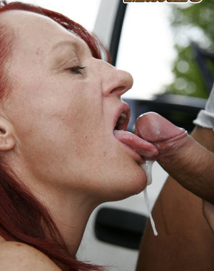 Red mature slut sucking cocks on a parking lot