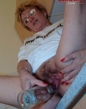 stuffing a big dildo in her mature cunt